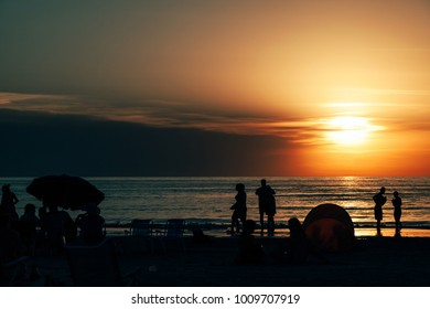 Piriapolis, Uruguay - 16 January 2014: Silhouettes of people vacationing on the beach at the time of a gorgeous sunset