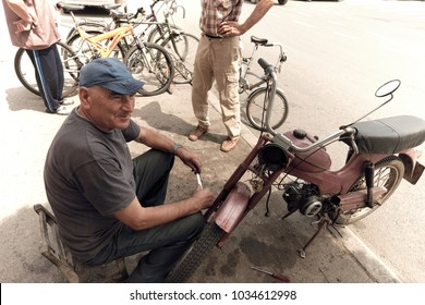 PIROT, SERBIA - JULY 27, 2017: a mechanic that repairs bicycles and old scooters is working on the sidewalk in front his workshop