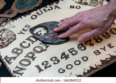 Pisa, Italy - 2015, January 1: Occult priest during a private session, using an Ouija, also known as a spirit board or talking board.