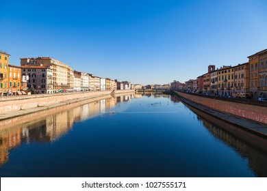 PISA, ITALY - DECEMBER 21, 2017: Arno river embankment with colorful old houses in Pisa. Picturesque medieval town of Pisa from bridge Ponte di Mezzo, Tuscany, Italy.