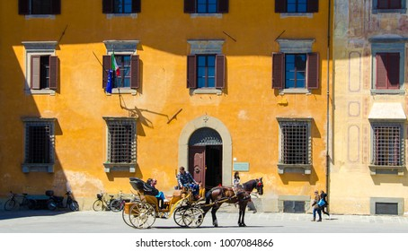 Pisa, Italy - MAY 1, 2017: horse-drawn carriage for tourists behind a colourful building in historical center of Pisa