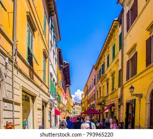 Pisa, Italy - May 1 2017: People are walking on the narrow colourful Italian street