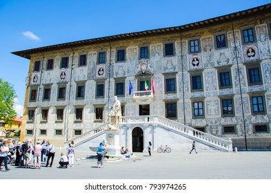 Pisa, Italy, May 1 2017: Group of tourists are listening a guide behind of Scuola normale superiore in Pisa