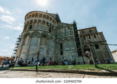 pisa, Italy - May, 17, 2017: Tourists sat in the sade provided by the Pisa Cathedral during a hot summer.