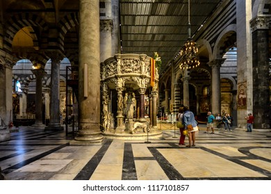 Pisa, Italy - September 22 2017: Tourists visit Giovanni Pisano's marble pulpit in the interior of the Santa Maria Assunta, Pisa's grand Duomo Cathedral in the Square of Miracles, in Pisa Italy