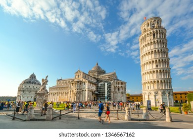Pisa, Italy - September 23 2018: Tourists fill the Field of Miracles and Cathedral square alongside the Leaning Tower, Baptistery and Duomo in the Tuscan city of Pisa, Italy