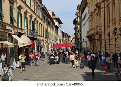 Pisa, Italy - September 28, 2017: People walk in a shopping street with stores and restaurants in Pisa, Italy on September 28, 2017