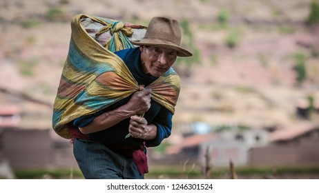Pisac, Peru - August 12 2011: An old man carrying a heavy bag of cereals.