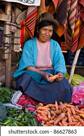 PISAC PERU - AUGUST 17: Quechua woman sells vegetables at a market in Pisac, Peru on August 17, 2008. Pisac Market in the Sacred Valley is a popular destination for tourism from all around the world.