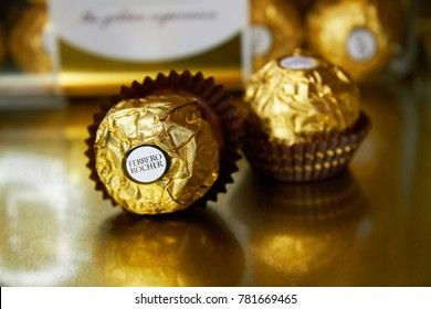 PISA/ITALY - 12/26/2017: Chocolate candies Ferrero Rocher. Golden wrappers. Chocolat with nuts. Golden, luxury delicious. Italian chocolate candy.
