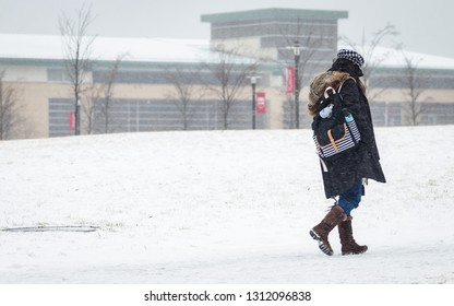 Piscataway, NJ - February 12, 2019:  Snow, sleet, and frozen rain fall as a student at Rutgers University walks on a snow covered campus.