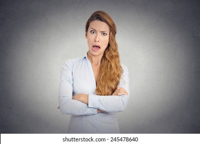 Pissed of angry young woman with disgusted face expression shouting on grey wall background