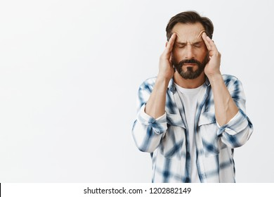 Pissed off man trying control anger, massaging temples with closed eyes, trying calm down, feeling headache or suffering from migraine, having bad day and asking for painkillers over gray background