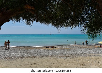 PISSOURI BAY, CYPRUS - JUNE 10, 2017: Tourists relaxing, sunbathing and swimming in the sea on the beautiful beach of Pissouri
