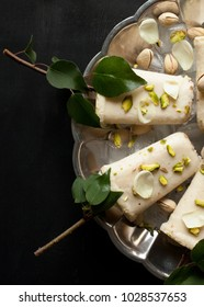 Pista kulfi, Indian ice cream on serving plate with ice cubes, pistachios, rose petals, tree branches with green leaves on black background, top view. Homemade sweet kulfi dessert.
