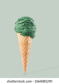 pistacchio ice cream with cone on green background