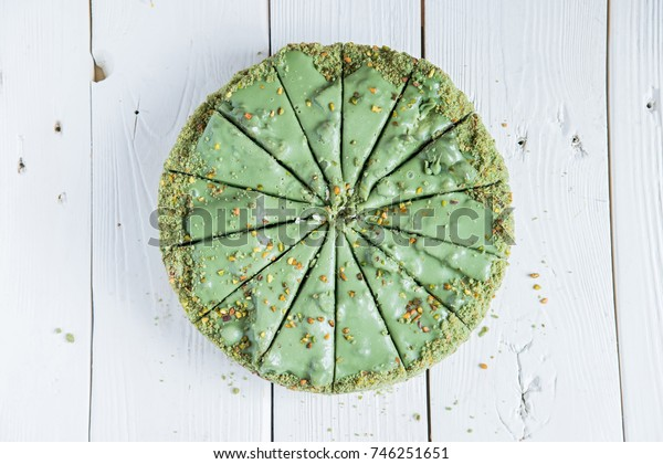 Pistachio cake sliced on white wooden background