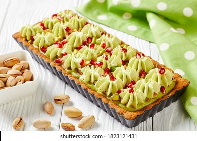 Pistachio ganache tart with pomegranate seeds on a square baking tin made of shortcrust pastry and whipped white chocolate pistachio filling served on a white wooden table, top view, close-up
