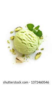 Pistachio Ice Cream isolated on white background, top view. Green pistachio gelato with pistachio nuts and mint.