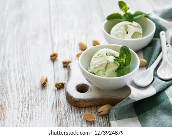 pistachio ice cream and mint with pistachio nuts on a old wooden background