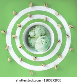 pistachio ice cream in a white plate on a striped pistachio background with scattered pistachios