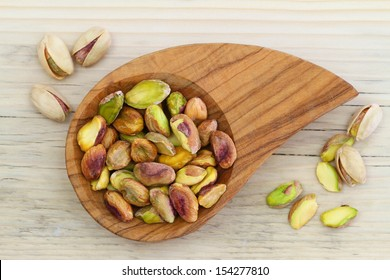 Pistachio nuts without shell in wooden bowl
