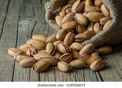 Pistachio in nutshell on black wooden rustic backdrop in burlap sack, composition of pistachios great for healthy and dietary nutrition. Concept of nuts