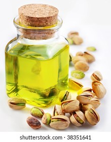Pistachio oil with nuts on a white background