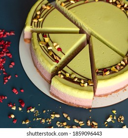 Pistachio and raspberry cheesecake decorated with chocolate and beans. Dark blue background. green and pink cheesecake portion cutting dessert closeup
