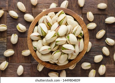 pistachio in shell nuts in bowl on wooden table background.