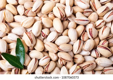 Pistachios background. Pistachio texture with leaves. Nuts. Top view