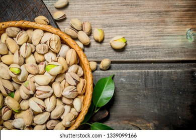 Pistachios in a basket with leaves. On a wooden background.