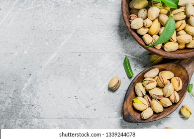 Pistachios in the bowl. On a rustic background.