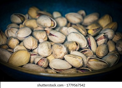 Pistachios in a ceramic bowl in a vintage photo with harsh vignette. Pistachio is a healthy vegetarian protein source. Natural nuts snacks.