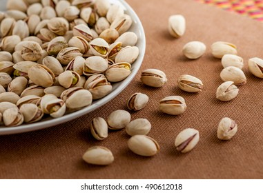pistachios  in a dish on the wooden floor.