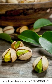Pistachios with green leaves . On a Wooden background.