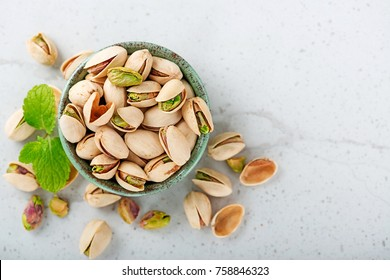 Pistachios nuts on gray background, top view