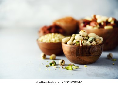 Pistachios nuts in wooden bowl. Food mix background, top view, copy space, banner. Assortment of nuts - cashew, hazelnuts, almonds, walnuts, pistachio, pecans, pine nuts, peanut, raisins.