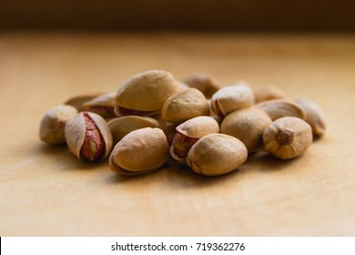 Pistachios on a wooden table in window light.