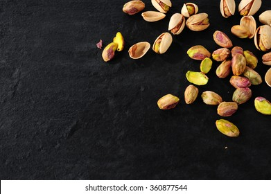 pistachios over dark slate background