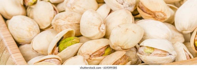 Pistachios - Roasted and salted pistachio nuts in a bamboo bowl.