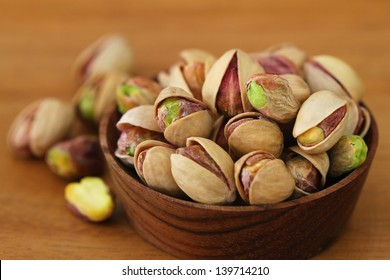 Pistachios with and without shell in wooden bowl