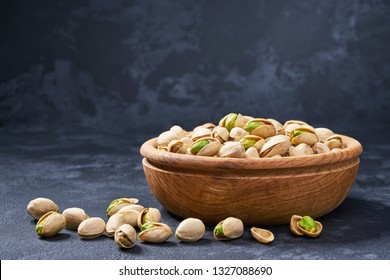 Pistachios in wooden bowl on black background. Organic pistachios, healthy food.