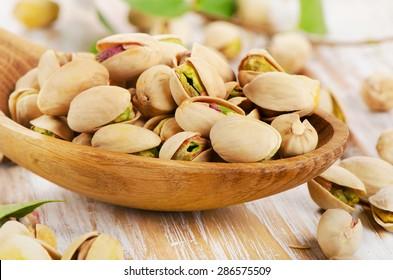 Pistachios in a wooden spoon. Selective focus