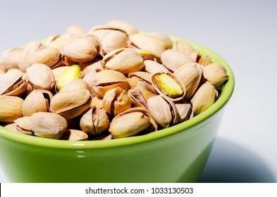 pistacio nuts in a bowl on white background