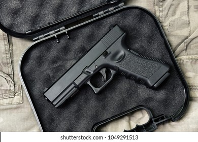 Pistol 9mm, Gun weapon series, Police handgun close-up on camouflage background.