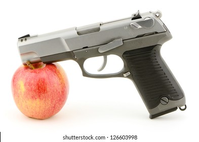 Pistol and apple studio concept shot for guns and school violence, mild relationship also guns and health