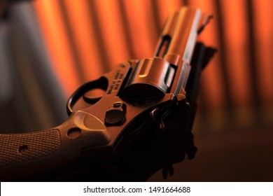Pistol automatic handgun weapon on table in hotel bedroom in atmospheric dark dramatic photo.