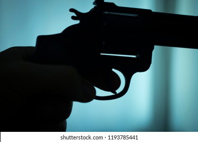 Pistol automatic handgun weapon in silhouette in hand of killer atmospheric dark dramatic photo.