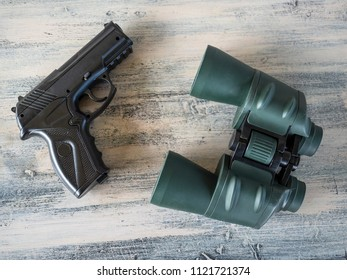 Pistol and binoculars on a wooden painted table